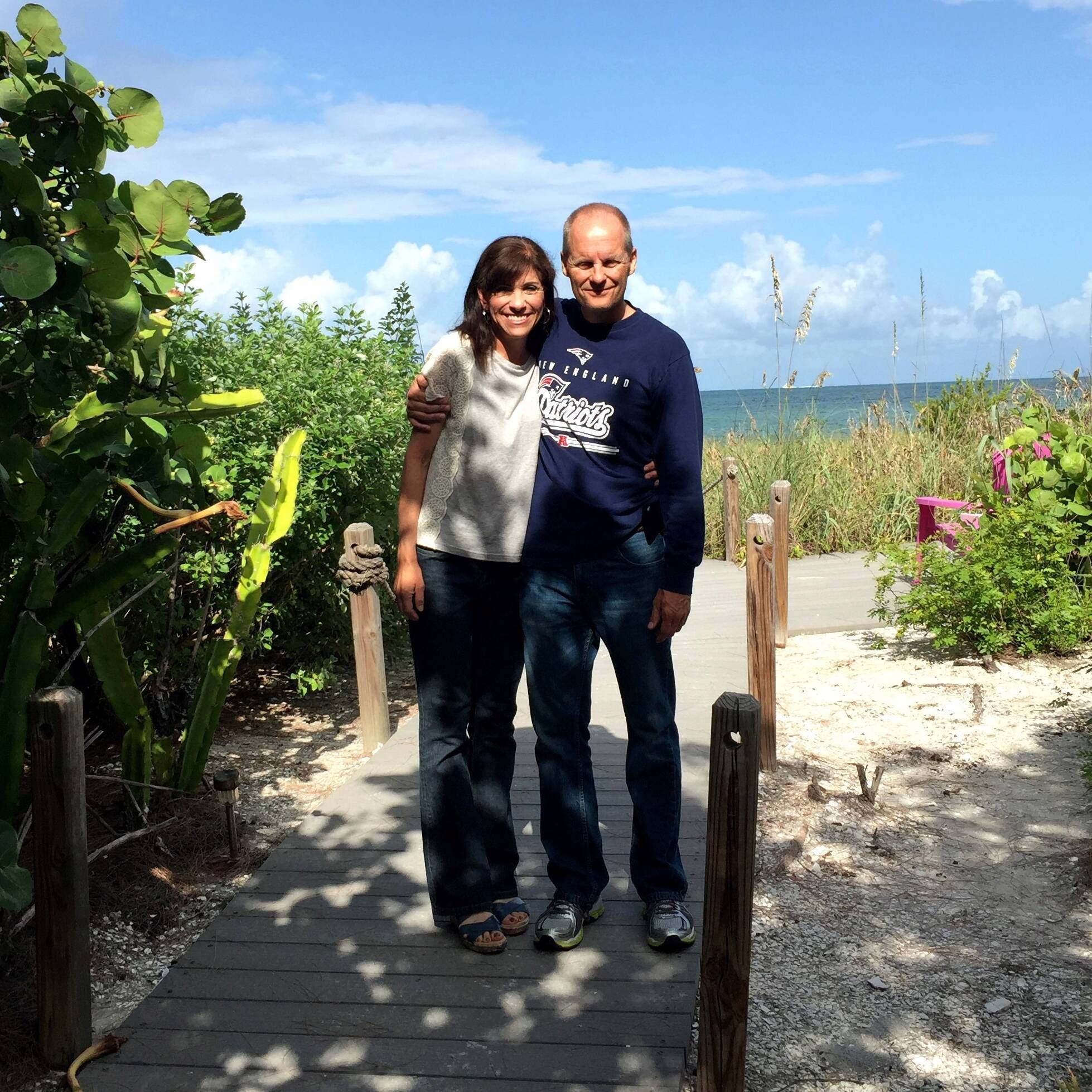two people standing on path in front of plants and ocean in background